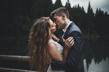 Beautifull Wedding Couple Kissing And Embracing Near Mountain With Perfect View