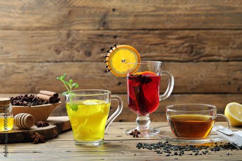 te' infuso tisana di erbe e frutta tre bicchieri su sfondo tavolo rustico di leg Canvas Print
