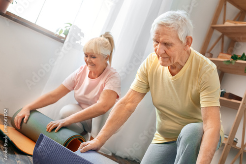 Senior couple exercise together at home health care rolling yoga mat ...