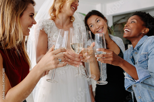 Woman in bridal gown toasting champagne glasses with friends Fototapete