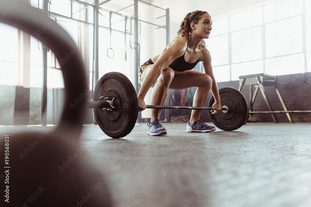 Fototapety, obrazy: Woman lifting a barbell at the gym