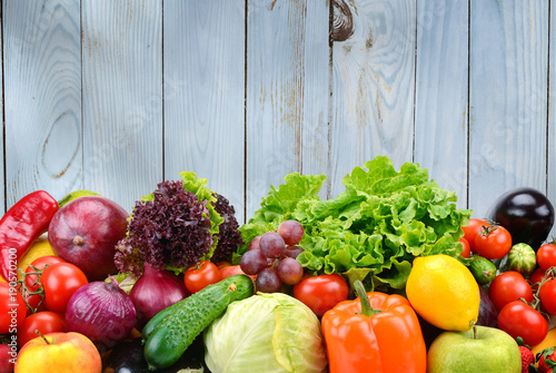 Useful vegetables and fruits on light blue wooden wall background © Serghei Velusceac