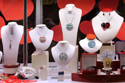 Naszyjniki, kolczyki i pierścień na białych popiersiach w sklepie jubilerskim.