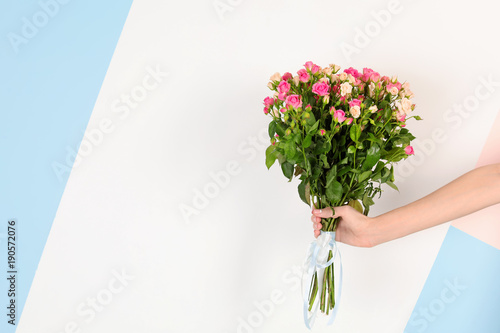 Wall Murals Floral Woman with beautiful bouquet of roses on color background