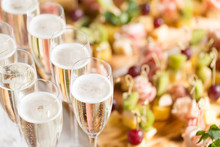 Furshet. Table Top Full Of Glasses Of Sparkling White Wine With Canapes And Antipasti In The Background. Champagne Bubbles