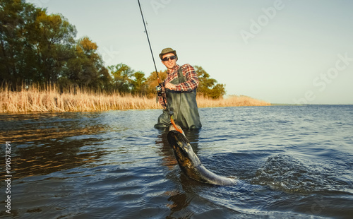 Fotografía  The fisherman is holding a fish pike caught on a hook in a freshwater pond