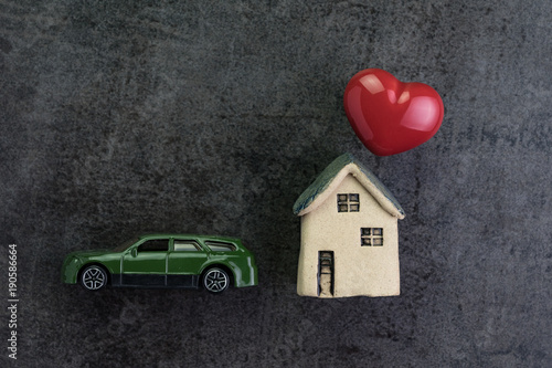 Fotografie, Obraz  Love house with ceramic miniature house and red heart shape and toy car on dark