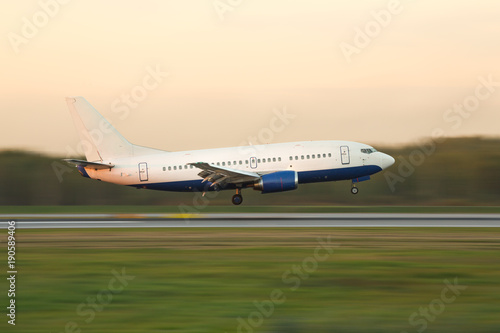 Fototapeta narrow-bodied passenger airplane landing at international airport during sunset, in motion, side view, copy space for text/ airplane climbs after take off/ Landing aircraft low over the runway obraz na płótnie