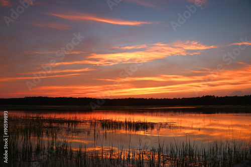 Huntington Beach State Park landscape.Dramatic sunset over the expansive salt marsh. Scenic view with amazing colors after sunset sky reflects in a calm water.Murrels Inlet,South Carolina,USA.