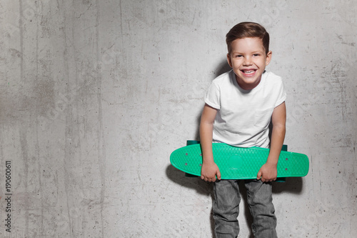 Fotografie, Obraz  Attractive little boy with green skateboard in his hands
