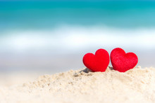 Valentine Concept.  Two Red Hearts On The Sand Summer Beach, Blue Background.