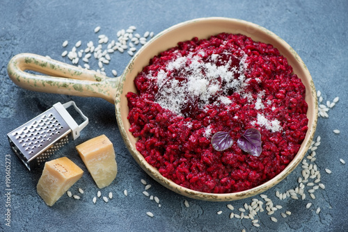 Beetroot risotto topped with baked beetroot slices and grated parmesan cheese, studio shot