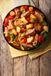 Asian food: Stewed beef with potatoes, peppers, peas, tomatoes and carrots close-up on the table. Vertical top view