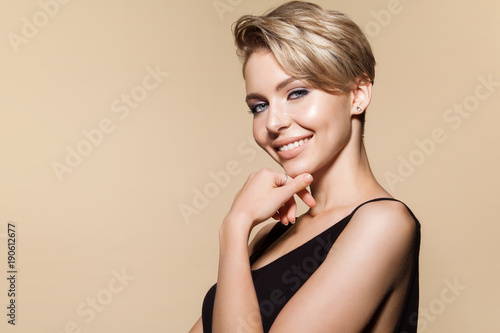 Fotografia Young smiling woman with modern short hairstyle, studio portrait