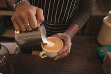 Barista Pouring Steamed Milk In A Cup At Counter
