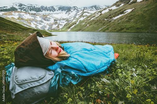 Photo Woman relaxing in sleeping bag laying on grass enjoying lake and mountains lands