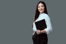 Beautiful Young Asian Businesswoman Holding Folder And Smiling At Camera Isolated On Grey