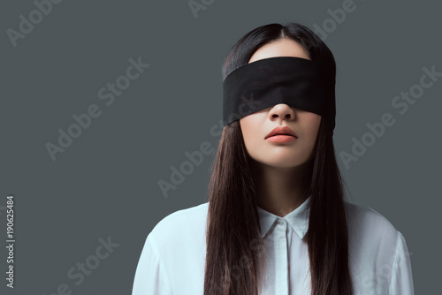 Photo young woman wearing black blindfold isolated on grey