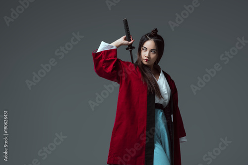 Photo  samurai in kimono holding katana sword and looking away isolated on grey