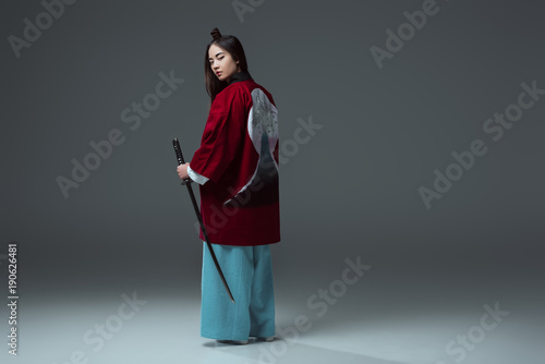 Valokuva back view of samurai in kimono holding katana and looking at camera on grey