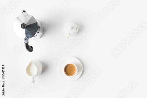 Fotografia top view of arranged cup of coffee, jag of milk and coffee maker on white surfac