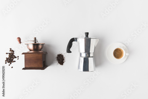 Obraz na plátně top view of arranged coffee making supplies, ingredients and cup of coffee on wh