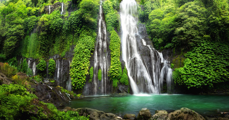 Jungle waterfall cascade in tropical rainforest with rock and turquoise blue pond. Its name Banyumala because its twin waterfall in mountain slope