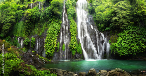 Printed bathroom splashbacks Waterfalls Jungle waterfall cascade in tropical rainforest with rock and turquoise blue pond. Its name Banyumala because its twin waterfall in mountain slope