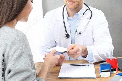 Fototapeta Wizyta u lekarza. Pacjentka w gabinecie lekarskim. Lekarz wpisuje zalecenia i recepty. obraz