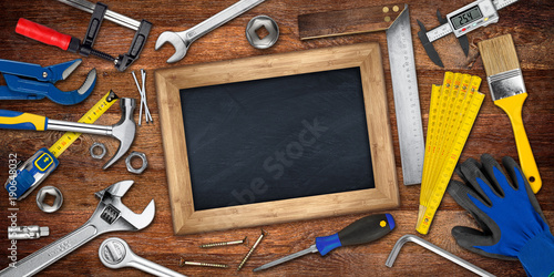 Valokuva  hand tools and empty blackboard chalkboard with copy space on wooden workshop ta