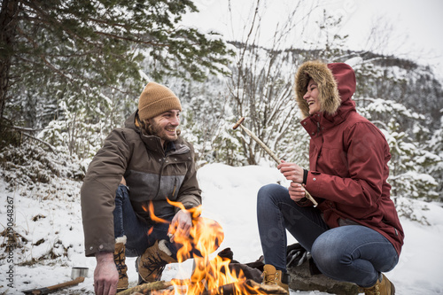 Happy couple on a trip in winter having a break at camp fire