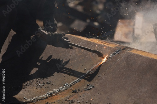 Worker cutting the metal in the scrapyard