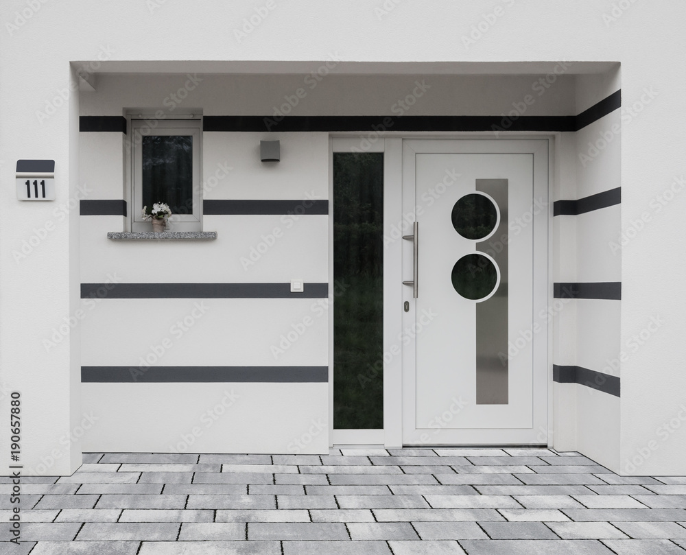 Fototapeta Moderner Eingang eines Hauses mit Haustür Fenster und Betonpflaster -  Modern entrance of a house with front door window and concrete pavement