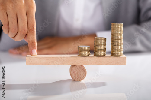 Fotografía  Businessperson Balancing Coins On Wooden Seesaw