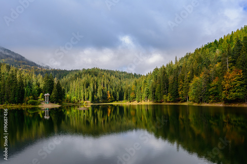 Spoed Fotobehang Reflectie View of Synevir high-altitude lake by autumn day. The leaf fall forest is reflected in water of lake.