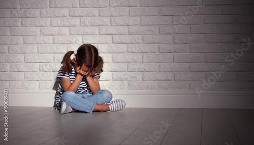 upset sad sad child girl in stress cries at an empty dark wall Wallpaper Mural