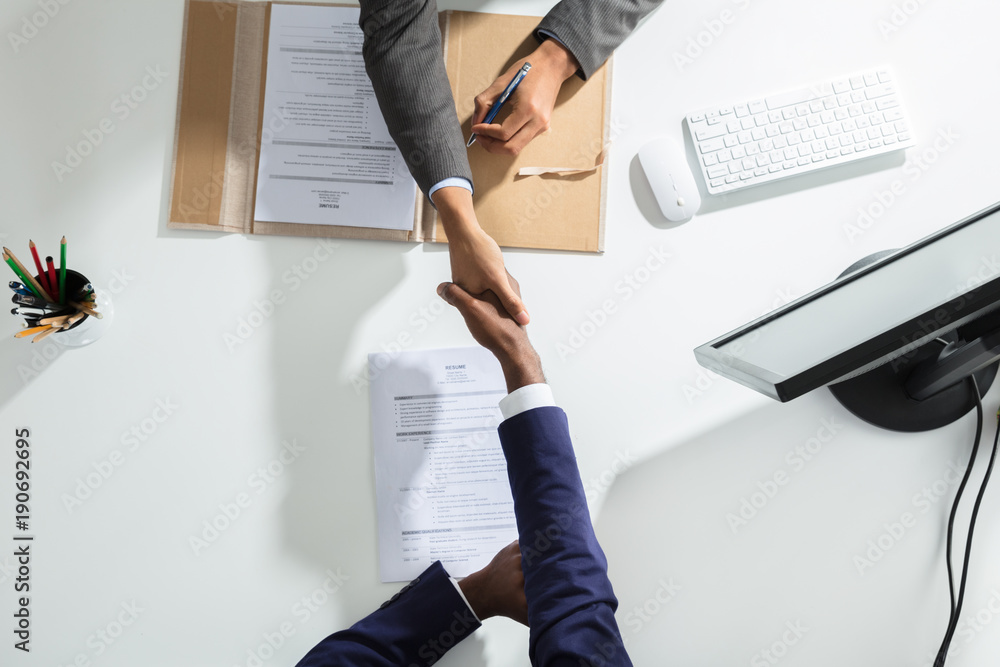 Fototapeta Businessperson Shaking Hand With Candidate Over White Desk