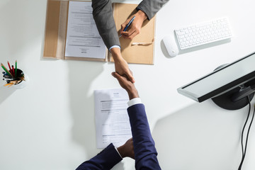 Businessperson Shaking Hand With Candidate Over White Desk