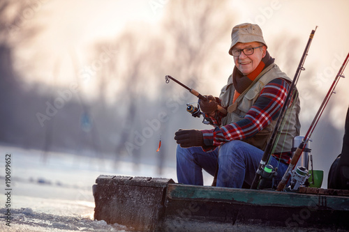 Printed kitchen splashbacks Fishing portrait of fisherman with fishing rod sit on frozen river in the winter