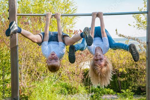 zwei gesunde Kinder turnen draußen und trainieren ihre Muskeln und Balance