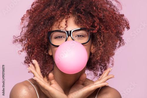 Obraz Afro girl blowing bubble gum balloon. - fototapety do salonu