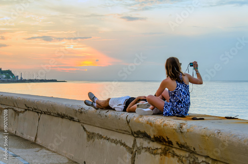 Photo Stands Havana Young couple watching and photographing the sunset on the ocean