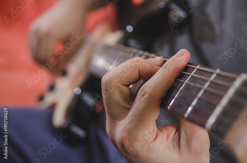 Fotografia, Obraz  Musician hands playing chords on electric guitar