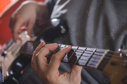 Fotografia Musician hands playing chords on electric guitar