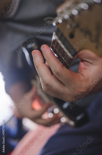 Fotografering  Musician hands playing chords on electric guitar