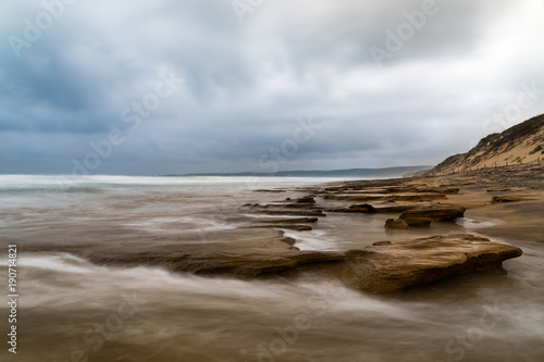 Photographie  Long exposure seascape of ocean and rocks with dramatic cloudy sky, Anglesea, Vi