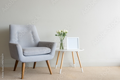 Fotografie, Obraz  Retro armchair and small round table with roses in glass vase and blank square f