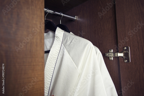 White bathrobe with hanger in wardrobe at hotel room Canvas Print