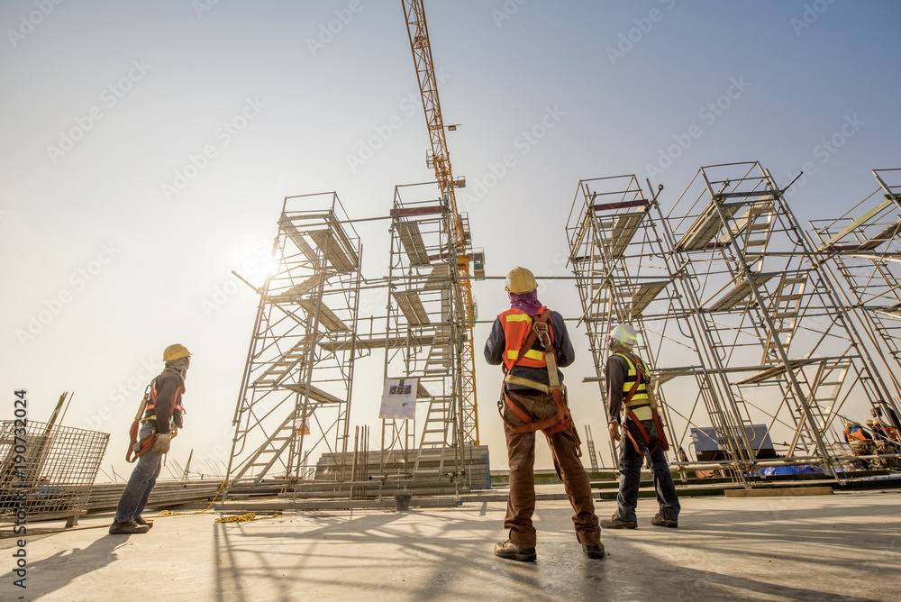 Fototapety, obrazy: Construction engineers supervising progress of construction project stand on new concrete floor top roof and crane background