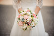 beautiful bride in a white dress holds bouquet outdoors